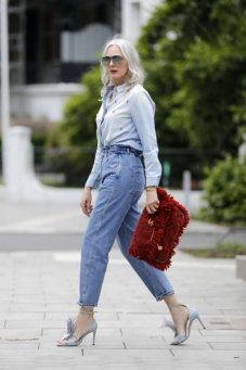 HAMBURG, GERMANY - JUNE 11: Best Ager Model and Influencer Petra van Bremen wearing sunglasses by Porsche Design, a light blue denim jeans shirt with silver embroidered beads by H&M, blue high waisted denim jeans by Mango, light blue sandals with feathers by Zara and a red and gold bag by Chanel during a street style shooting on June 11, 2020 in Hamburg, Germany. (Photo by Streetstyleograph/Getty Images)