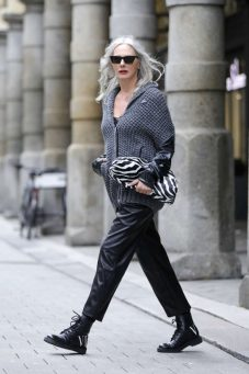 HAMBURG, GERMANY - JUNE 11: Best Ager Model and Influencer Petra van Bremen wearing sunglasses by Saint Lauent, a grey knitted jacket with leather sleeves by Ki6? Who are you?, black leather pants by Zara, a pouch bag with zebra pattern by Bottega Veneta, and black boots by Valentino during a street style shooting on June 11, 2020 in Hamburg, Germany. (Photo by Streetstyleograph/Getty Images)